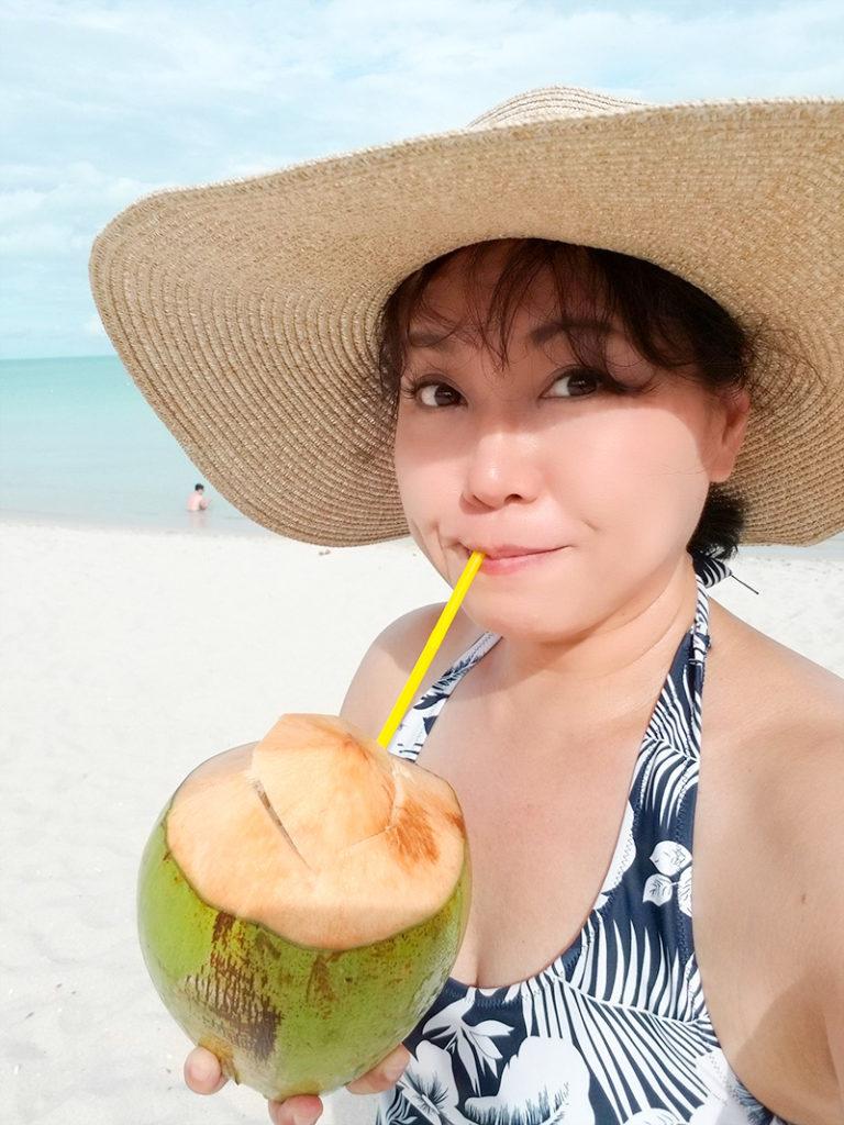 はじめてのリゾートホテルのプライベートビーチでココナッツジュースを飲む51歳